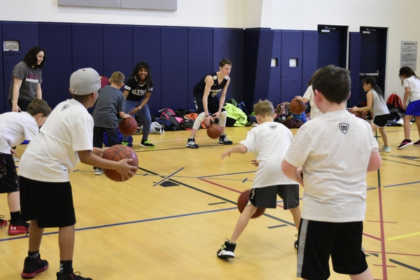 High school students showing elementary students how to dribble a basketball.